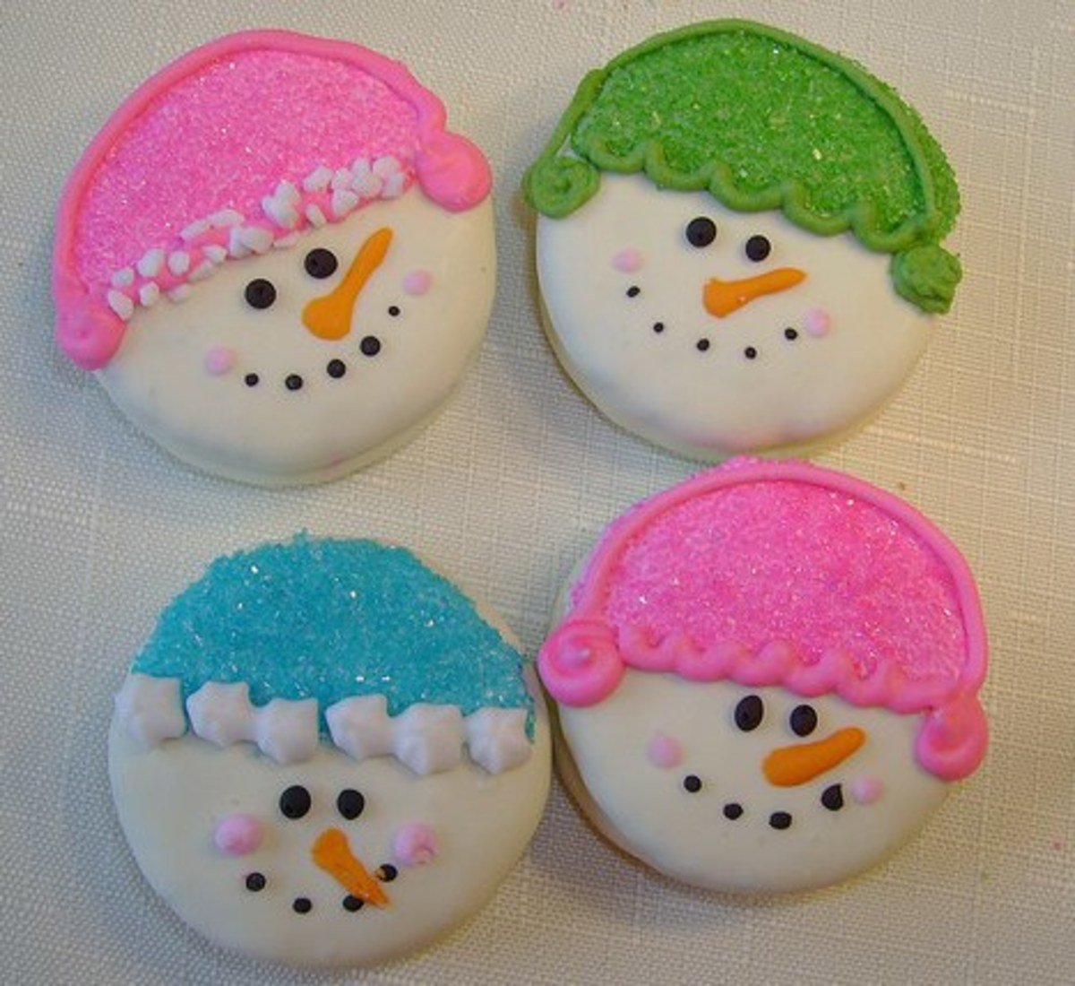 Easy snowman cookies made from Oreos dipped in white chocolate. Hats made from colored sprinkles.