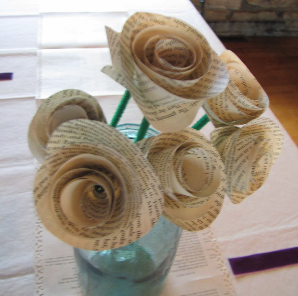 My niece, a librarian, had a book themed wedding, since she is a librarian. The runners down the center of the tables were book pages with artful edges (scrapbooking technique) and she made roses from book pages for centerpieces.