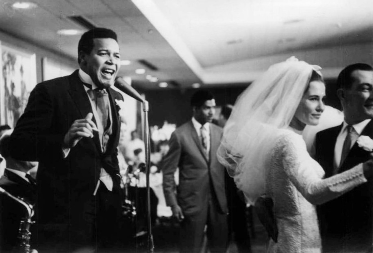 Photo of Chubby Checker singing at his wedding reception while his new bride, Catharina Lodders, dances with a guest. Chubby Checker was married in Philadelphia April 12, 1964.