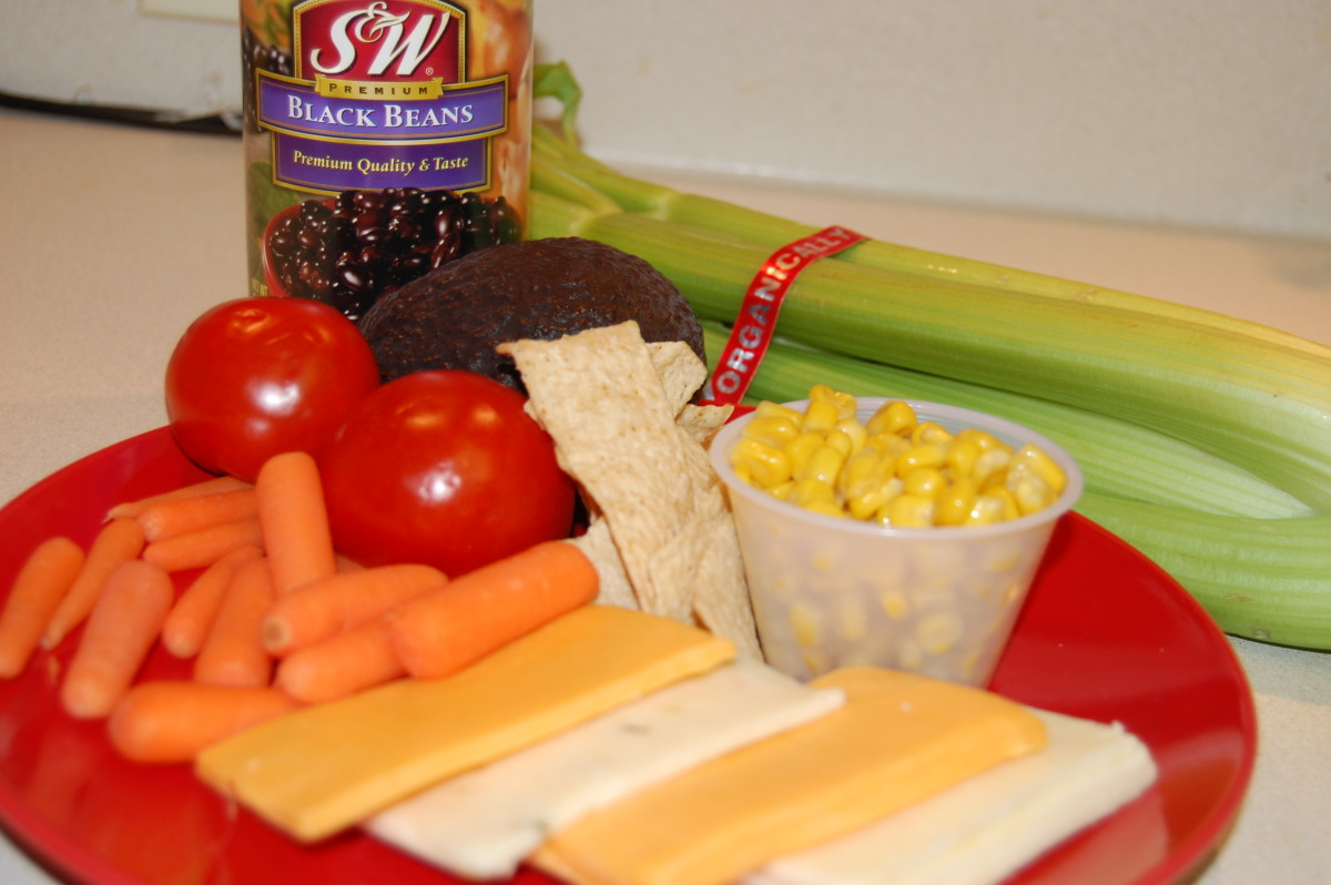 Tomatoes, carrots, celery, corn, avocado, black beans, tortilla chips, and cheese