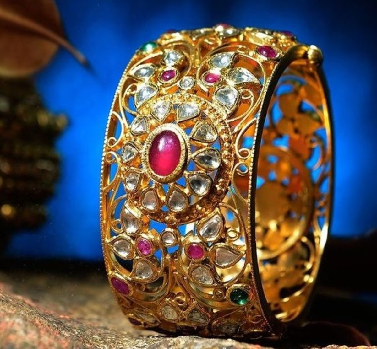 Unique intricate design on gold bangle with red ruby and white kunda