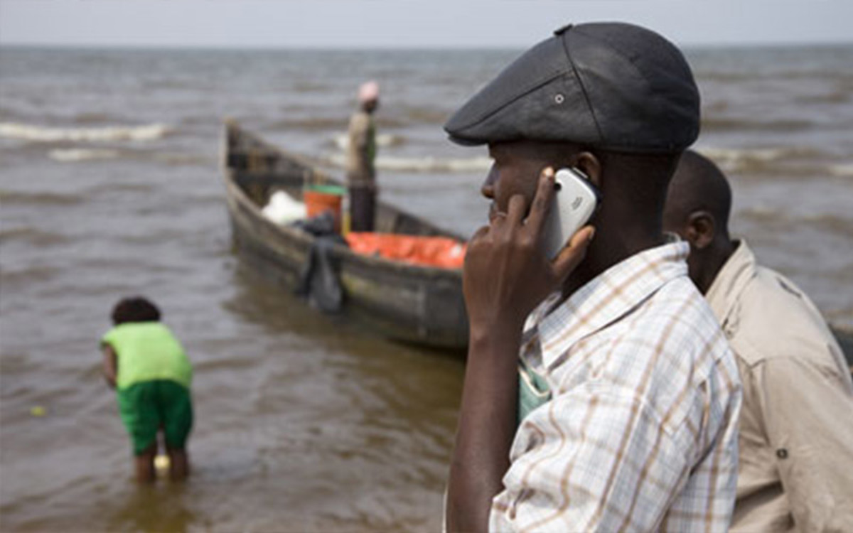 Boat owner  uses his phone to settle bills and pay local traders