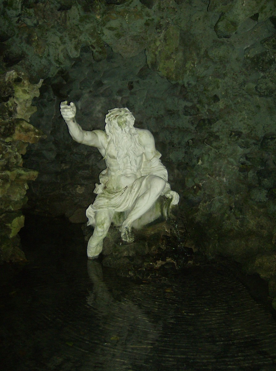 A statue sitting on a rock Inside one of the water grottos. These grottos are a great place to sit for a few minutes and cool off on a hot day.