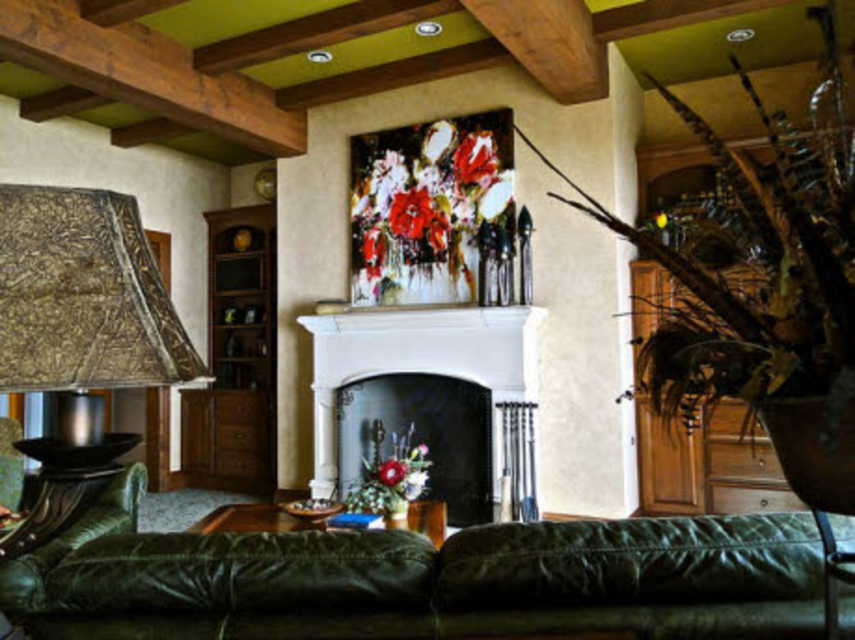 Wood beams in a traditional setting with a modern painting above the fireplace