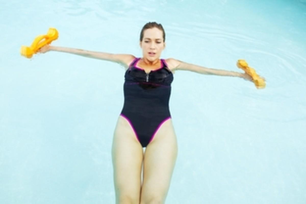 Ergo Bells in use - female in black one piece swim suite showcasing the use of the aquatic barbells