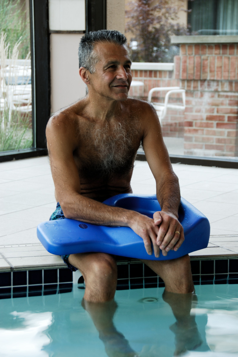 man sitting at the edge of the swimming pool with a body board in his lap