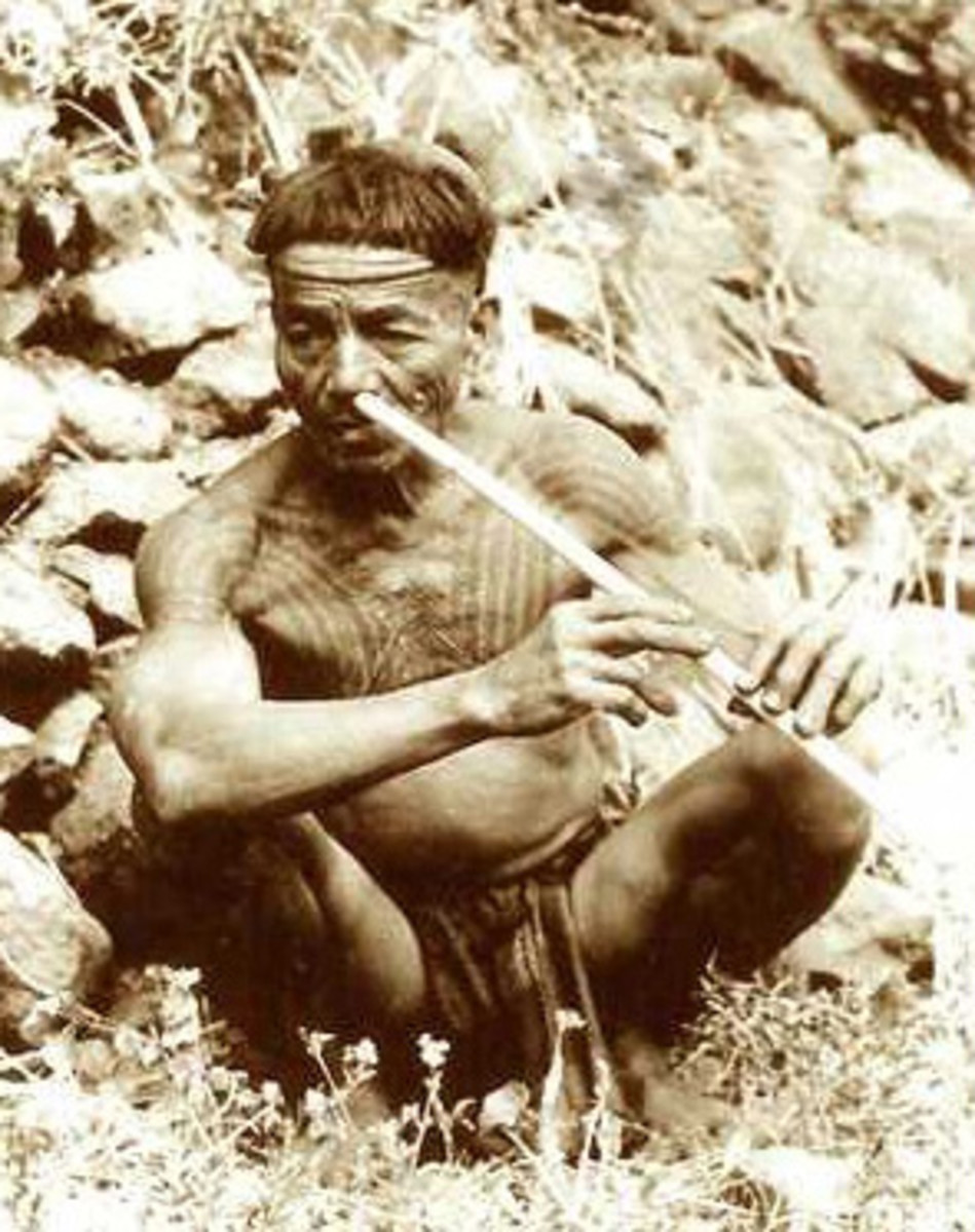 Warrior with Chaklag breast tattoo playing a nose flute