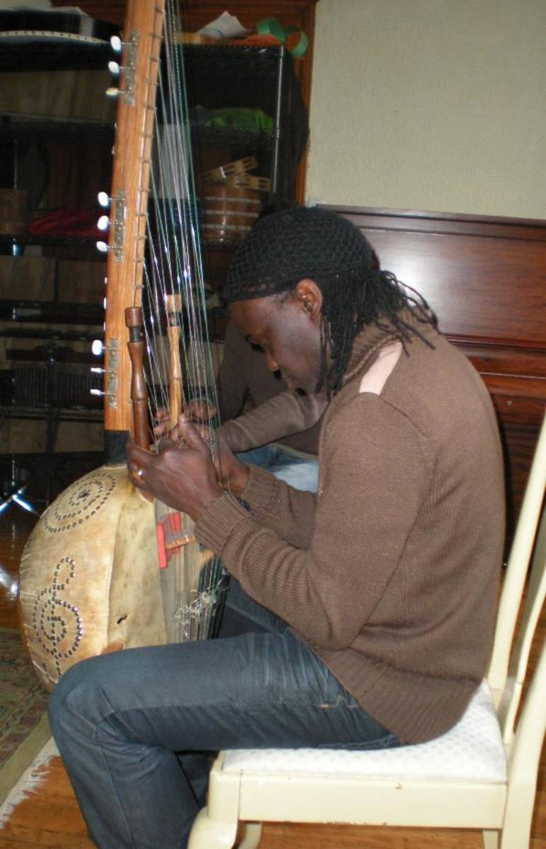 "Zal Sssokho(Senegal) playing the ""Kora"" (a 21 string Harp, and singing in both Malinke and Wolof languages that by traditions from West Africa"