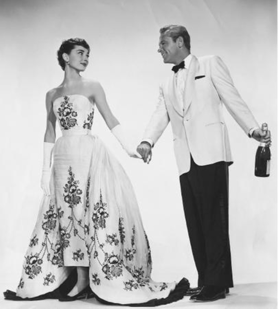 "In ""Sabrina"", wearing a Givency 'wedding dress', William Holden by her side."