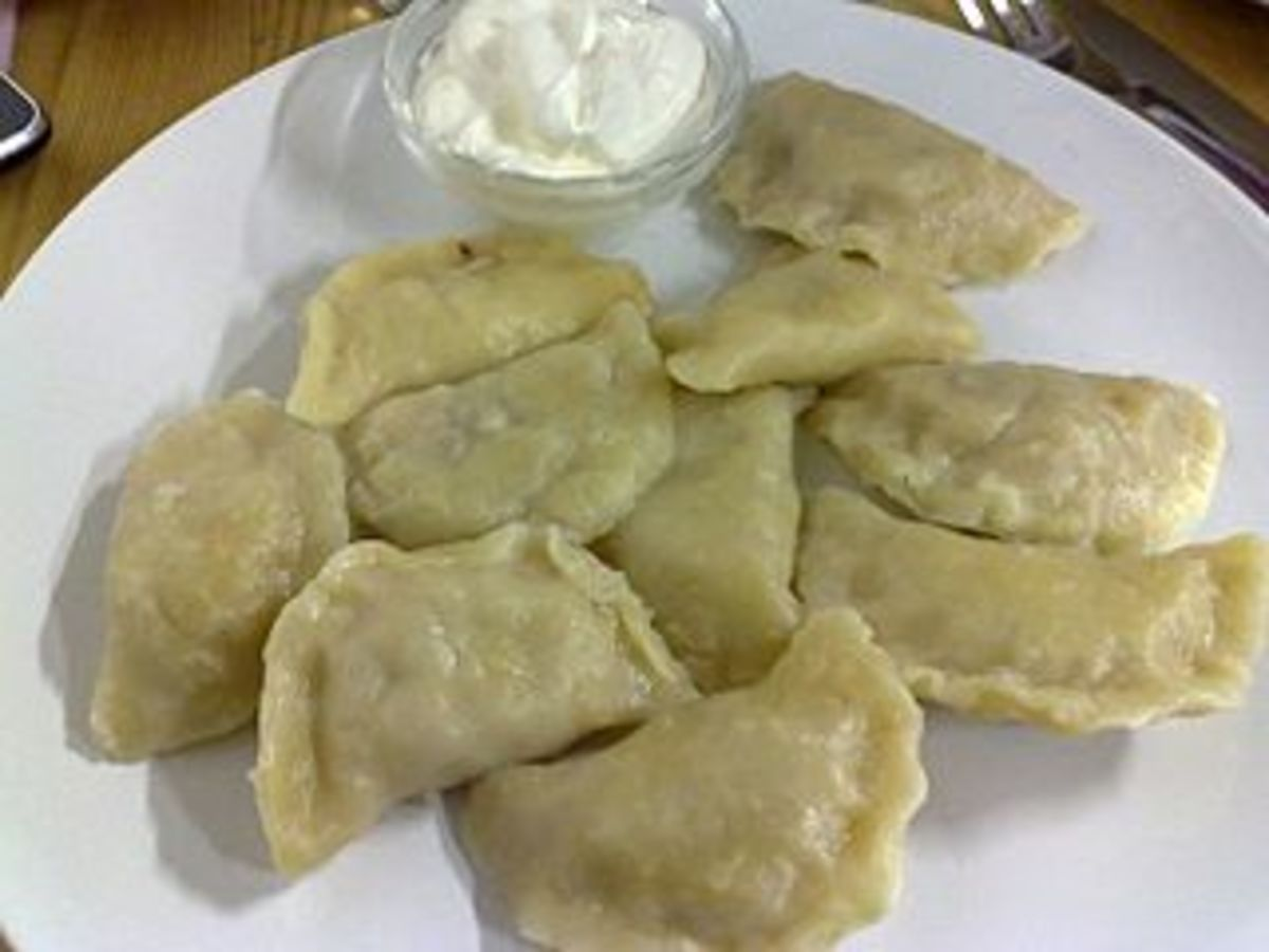 A plate of pierogies with sour cream.  Serve applesauce, too!