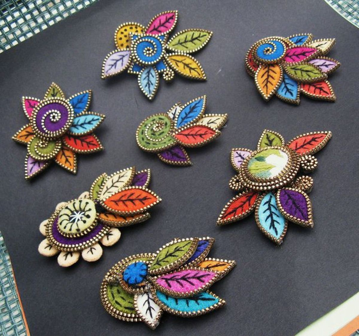 These gorgeous brooches are made with embroidered felt and zippers.