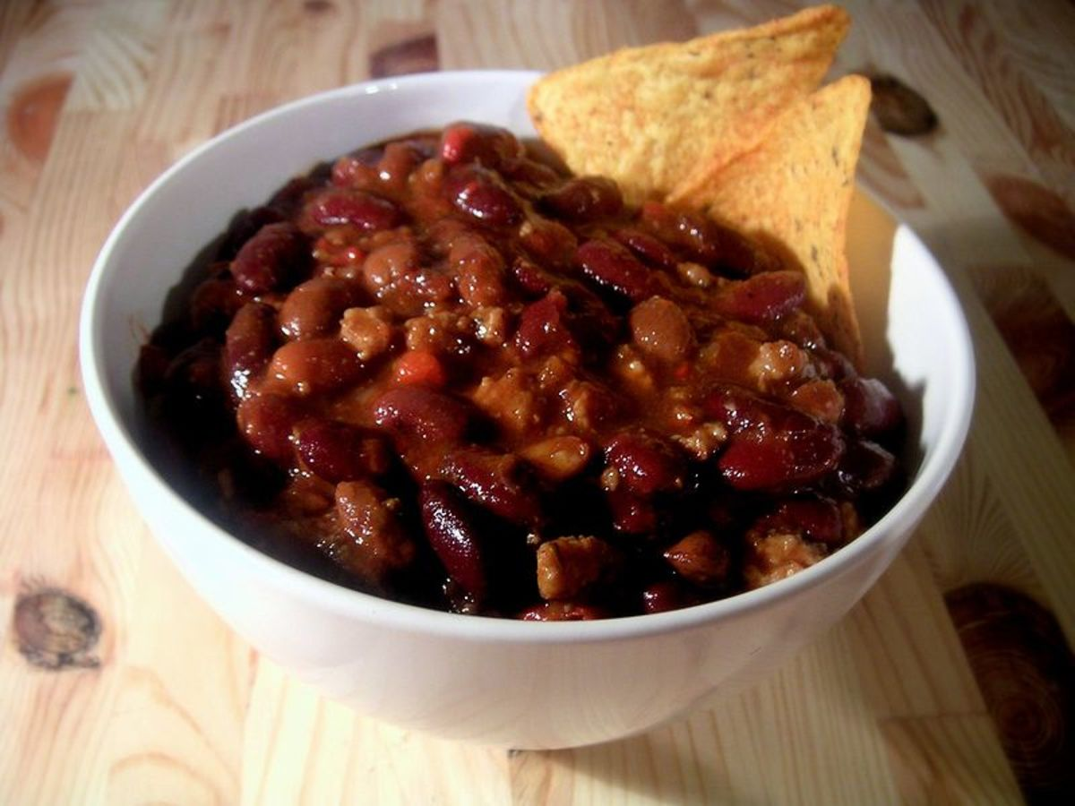 In the photo is a bowl of Chili served with tortilla chips. Notice the dark red color of this delicious chili.