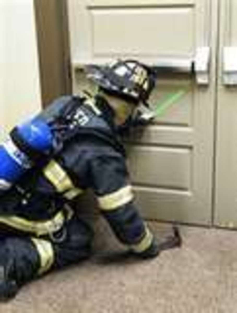 A firefighter initiates phase one of marking a door.