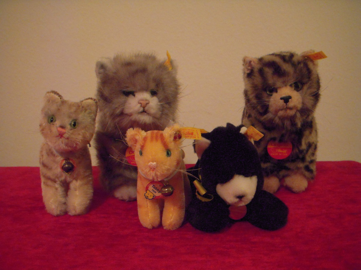 Two larger synthetic plush cats and one lying-down plush cat pose with their mohair counterparts.