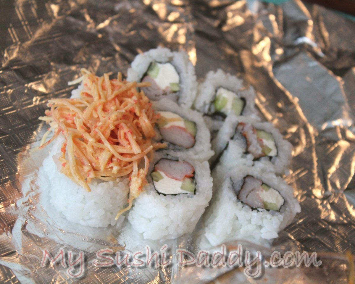Placing the seafood dynamite on top of the crab stick and cream cheese roll.