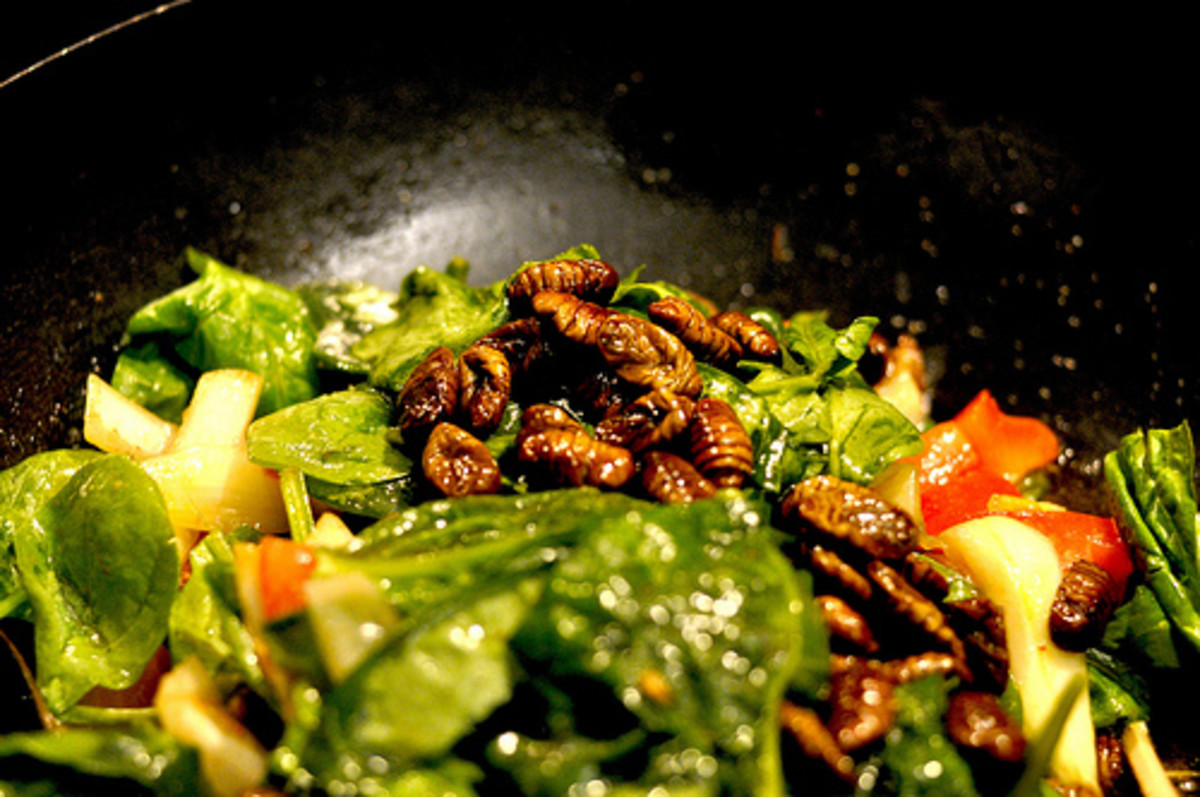 Silk worm larvae over mixed greens - Korean delicacy