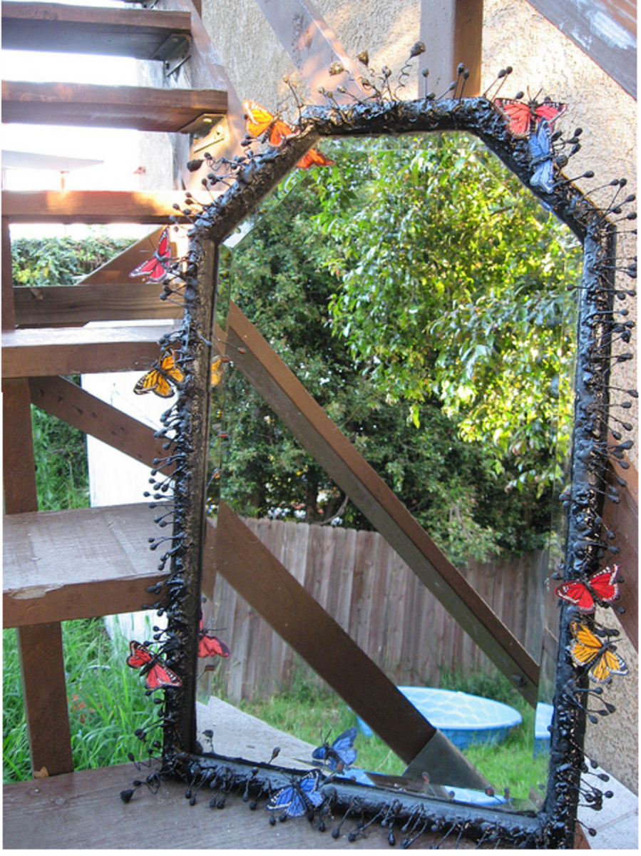 This mirror started with a plain frame, and the revamp consisted of a coating of black spray paint, plus faux flower stamens (I think) and fabric butterflies stuck all over to create a cool effect.