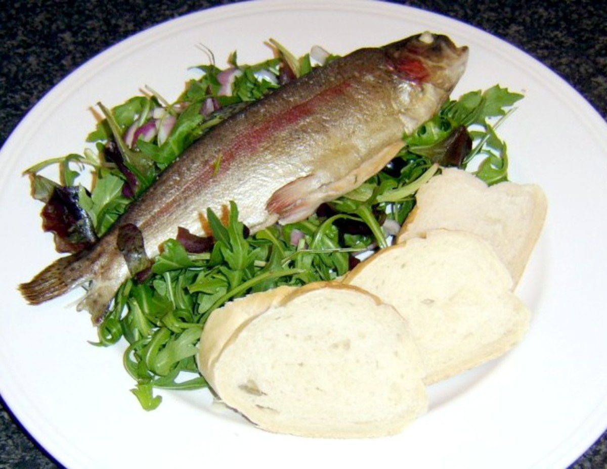 Whole rainbow trout steamed in white wine and served on a salad bed