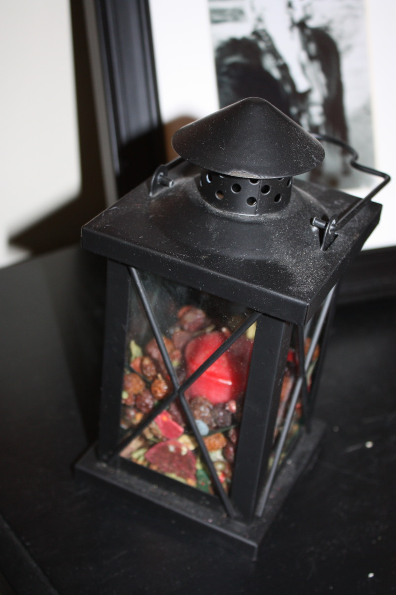 A rustic iron lantern filled with a candle and potpourri