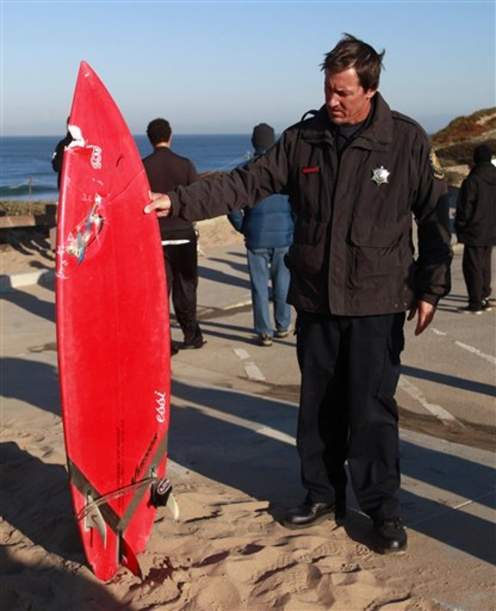 A California State Park lifeguard holds up the surfboard of Eric Tarantino, who neck and forearm was bitten. He was lucky the shark's teeth got the board and not him for this bite!