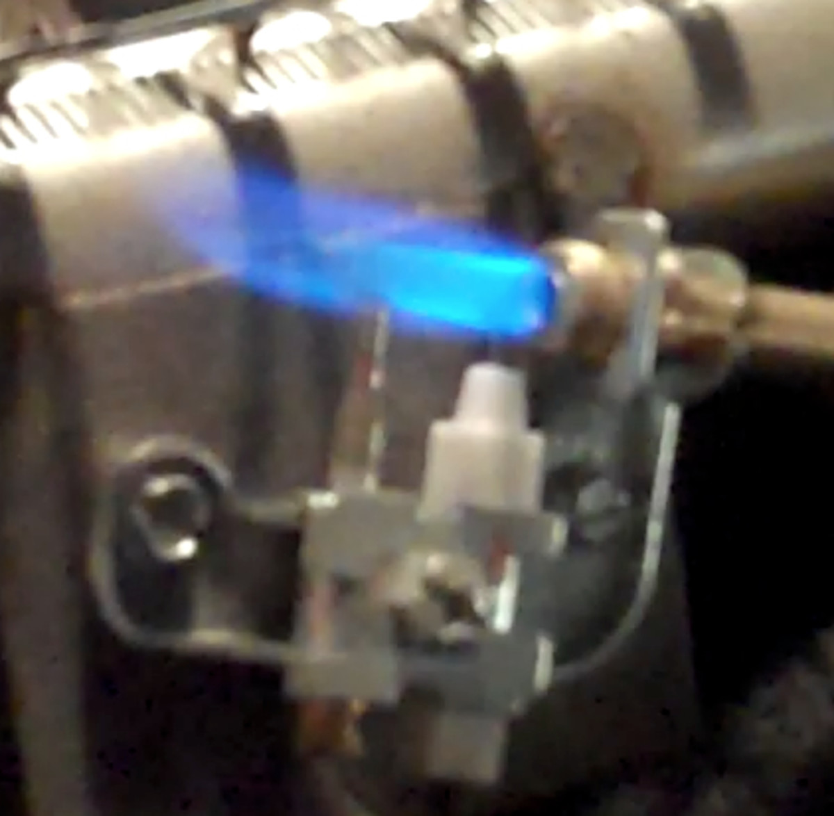 Ventless gas fireplace close up of pilot assembly showing the pilot flame, thermocouple and ignition electrode.