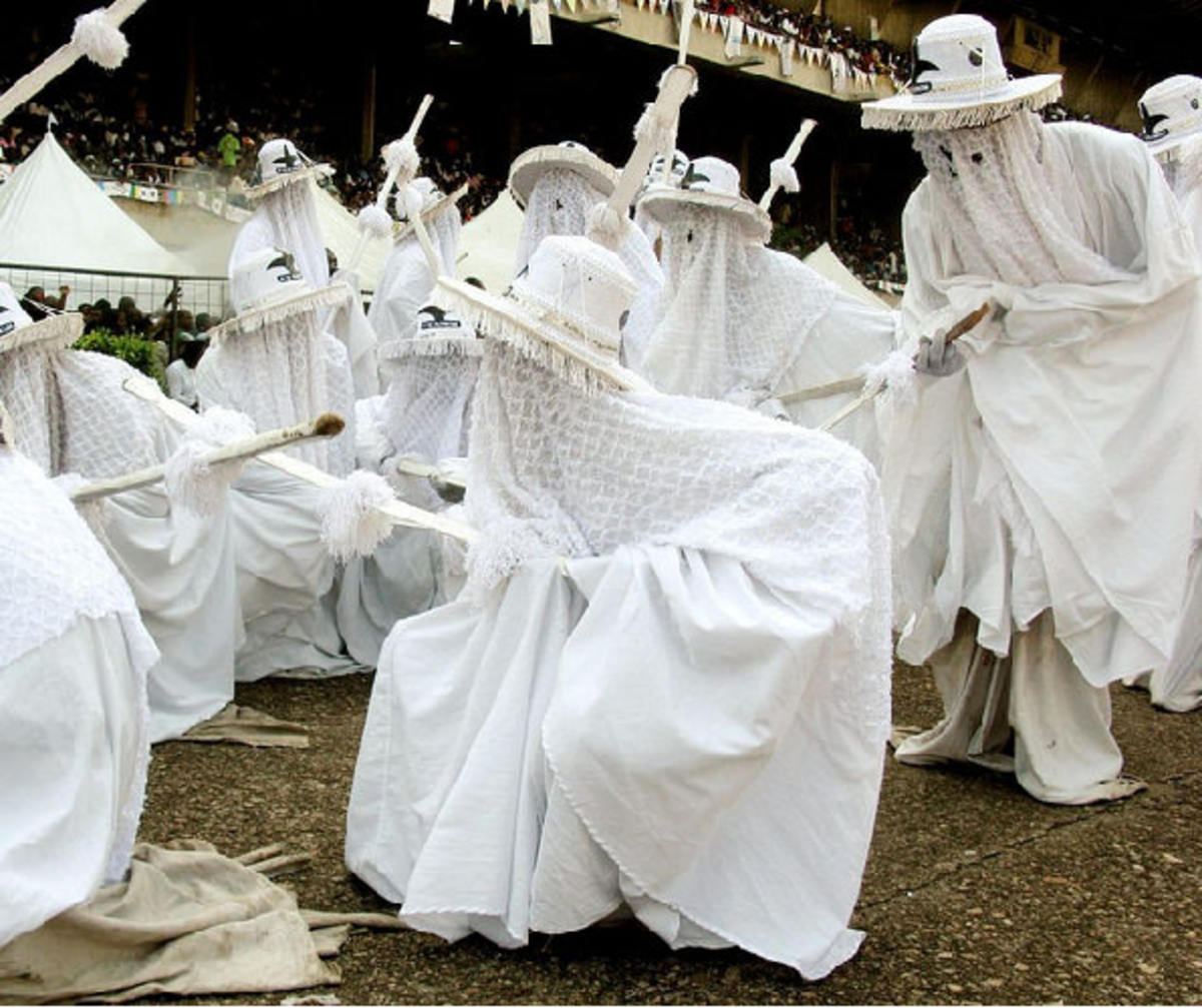 Eyo masquerades dancing to the beat of the drums, wearing the traditional all white regalia and wide-brimmed hats.