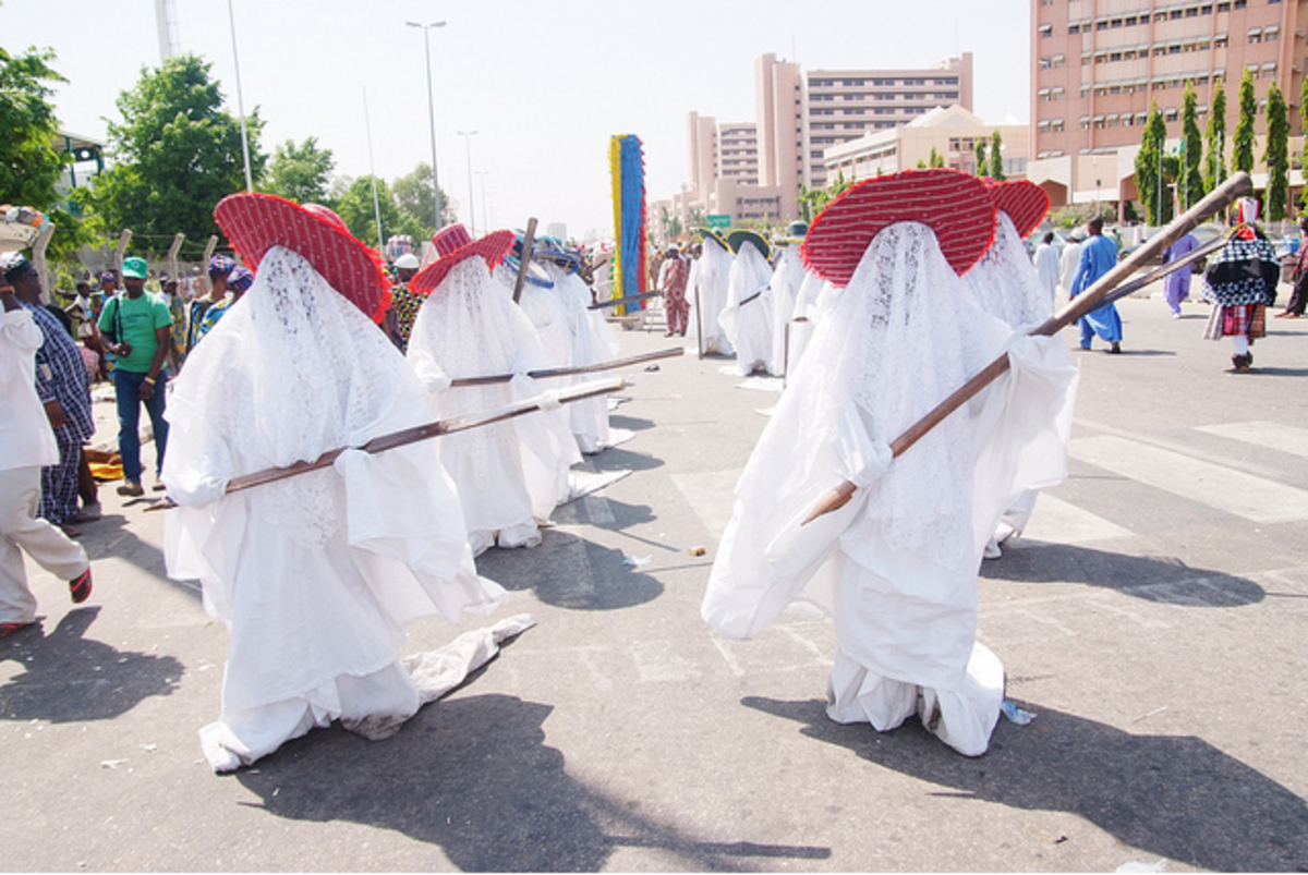 The Eyo masquerade's costume is one of splendour. White flowing robes, lace veils, prominent hats (different groups wear different hats), and the famous Opambata, a long thick cane that's a part of the ensemble.