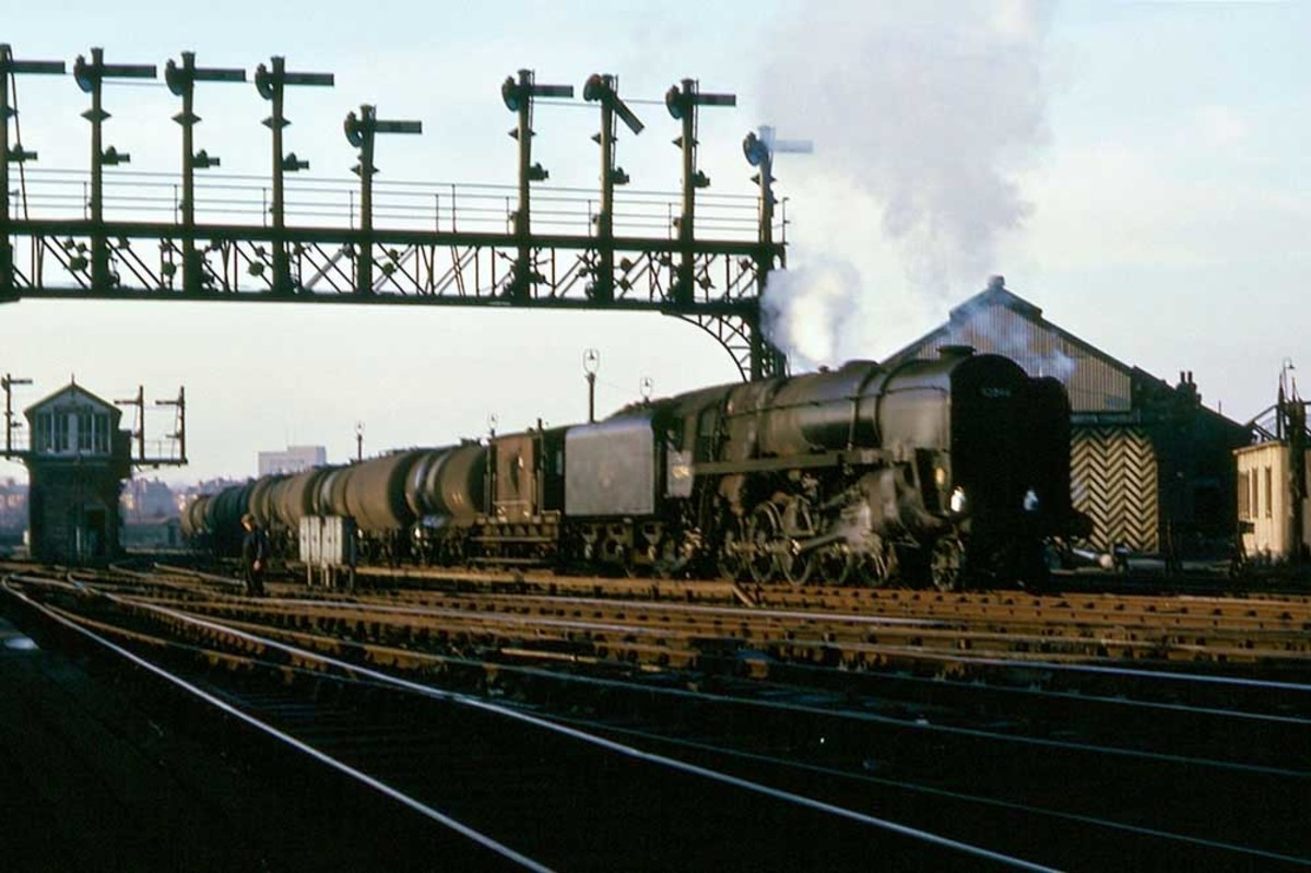 9F 2-10-0  92094 brings a train of oil tankers through Chester Station, January 1966 - topped and tailed with brake vans but no barrier wagons - possibly empties,   otherwise there'd be danger for both guards from explosion