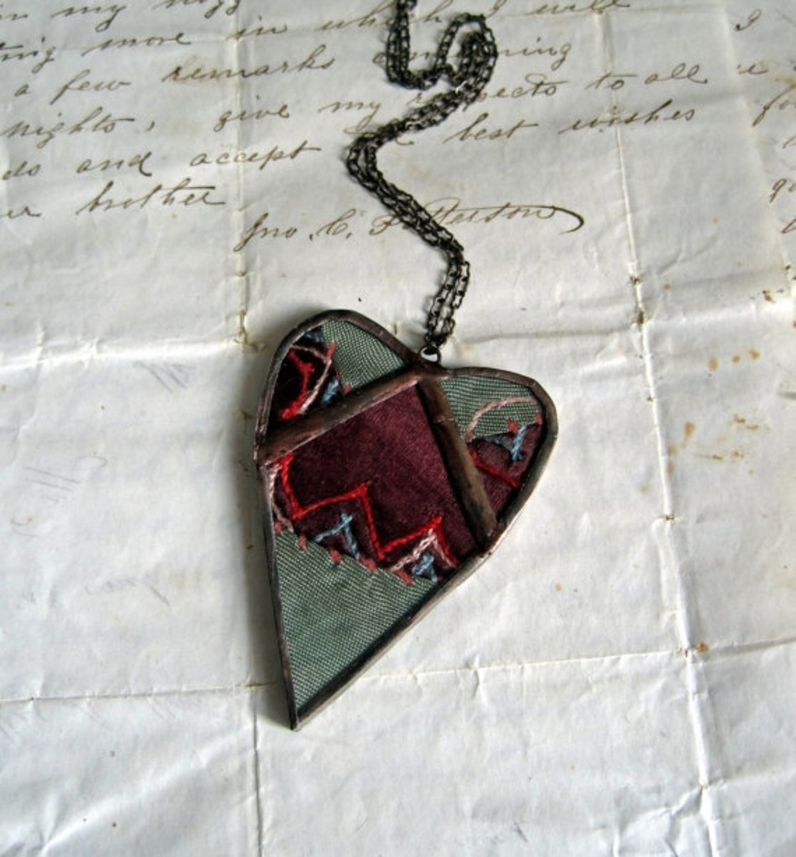 Necklace with a small piece of a crazy quilt under glass and soldered closed. Photo courtesy of     ThatOldBlueHouse2 at Etsy.