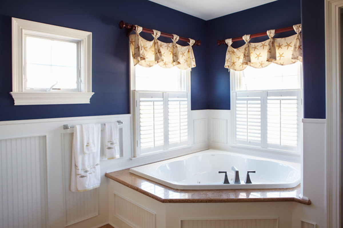 Nautical Themed Bathroom with Navy Blue Walls and White Wainscoating