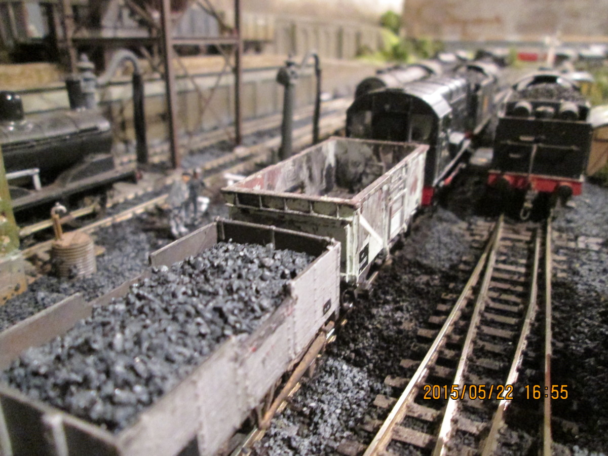 (Hornby) Dock Shunter with mineral wagons by the ash pit. The BR 16-tonner has one side door open for the man in the pit  to get going, shovelling cooled ash and cinders. This was one of several drawbacks with steam operation - dirt, dust and grease