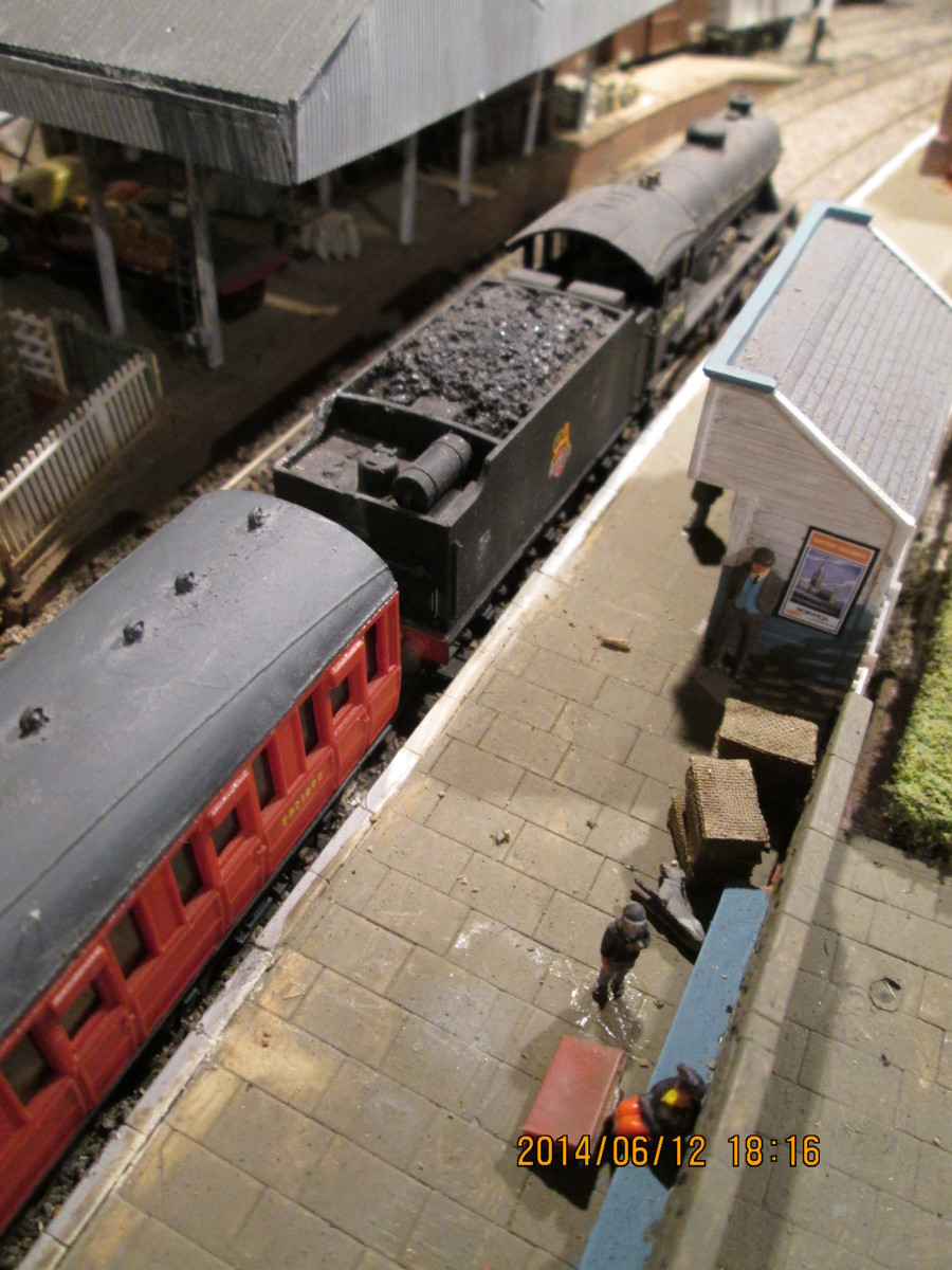 A look down on the platform towards the open fronted platform shelter (Hornby Skaledale range) beside D49/2 62764, 'The Garth' with her train of 1920s Gresley passenger stock. 'Brown boxes' by same platform shelter are pigeon baskets for forwarding