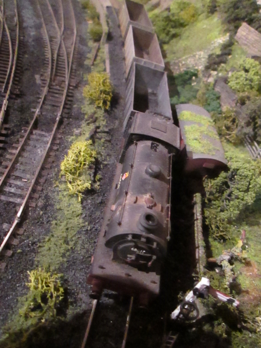 (Hornby) J94 68010 holds empty Loco Coal wagons at the short starter post, awaiting the right away.