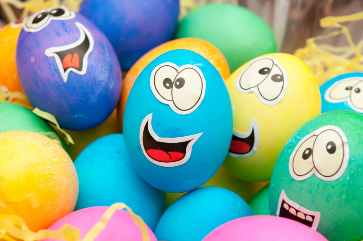 Using face stickers to design Easter eggs is fun and easy for toddlers.