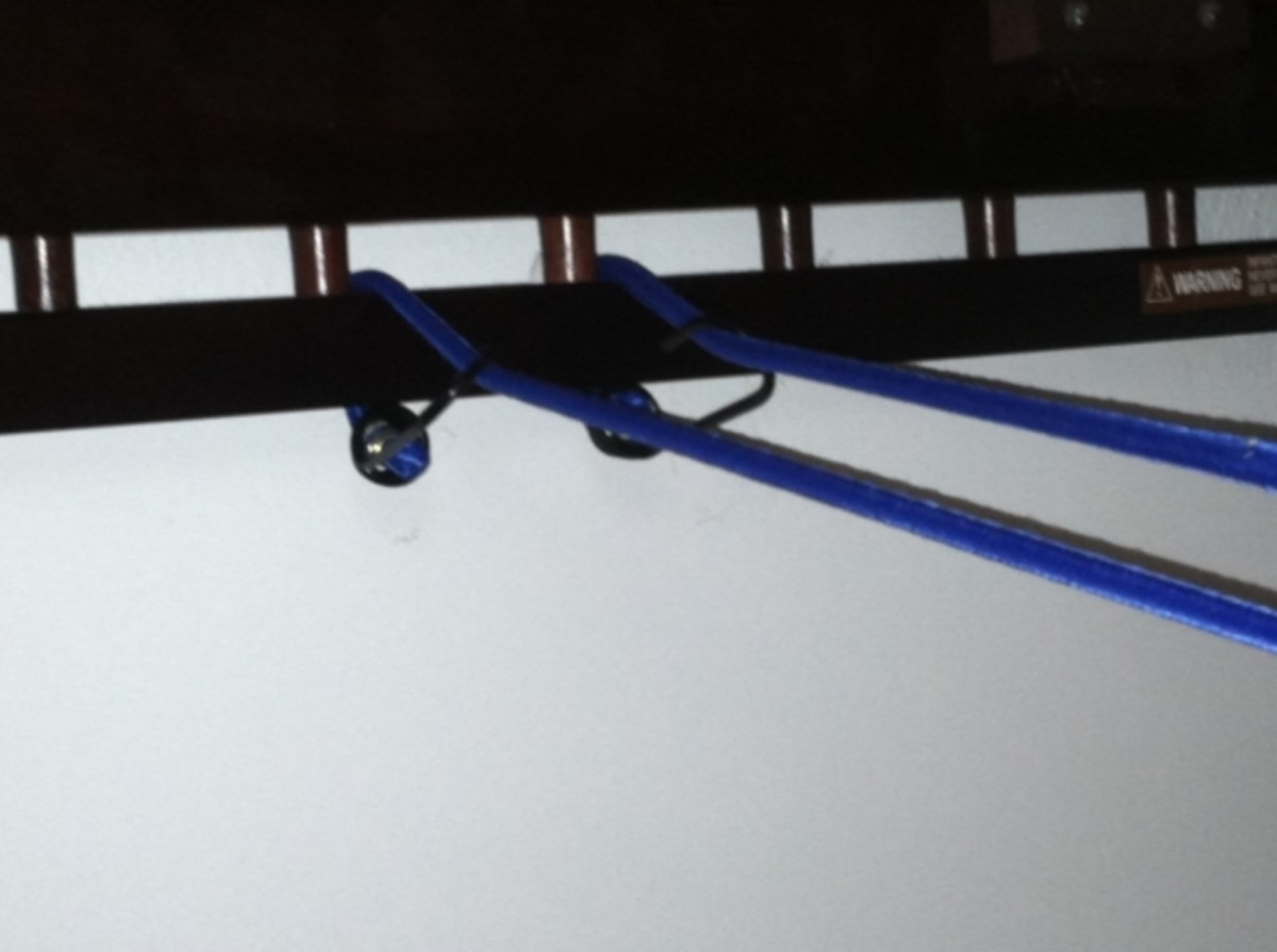 Attach one bungee cord  around the frame of the bed and back onto itself near one end of the rib.