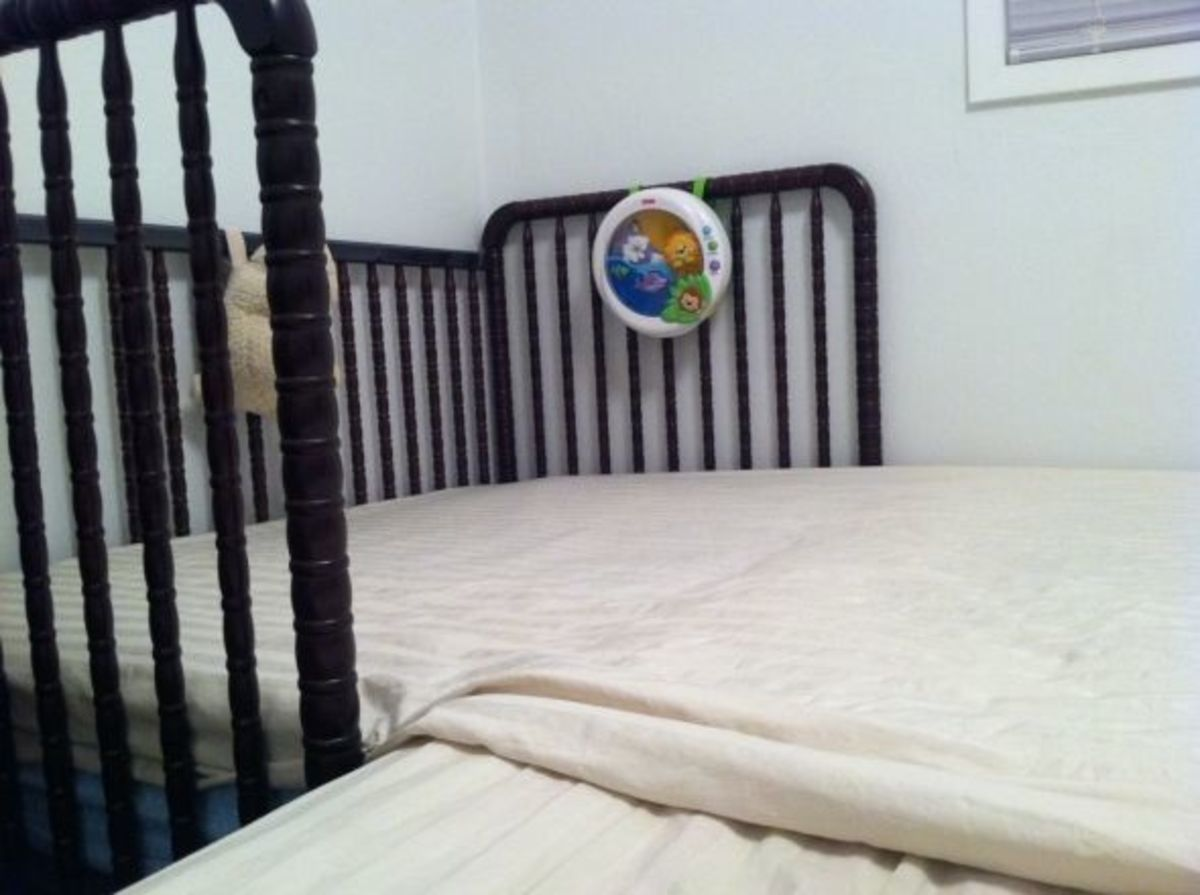 Take a sheet or blanket, fold it to just over the length of the crib and firmly tuck it in around the edges of the crib. Make sure it's long enough to cover the crack between the beds and it doesn't get bunched up while you move in your sleep (we use
