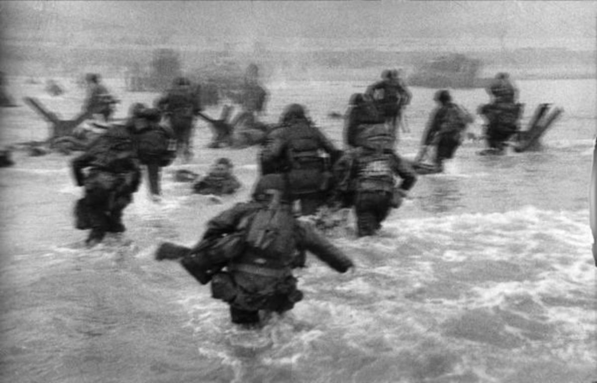 Soldiers struggle to get ashore. Note one soldier has already died and is floating in the water