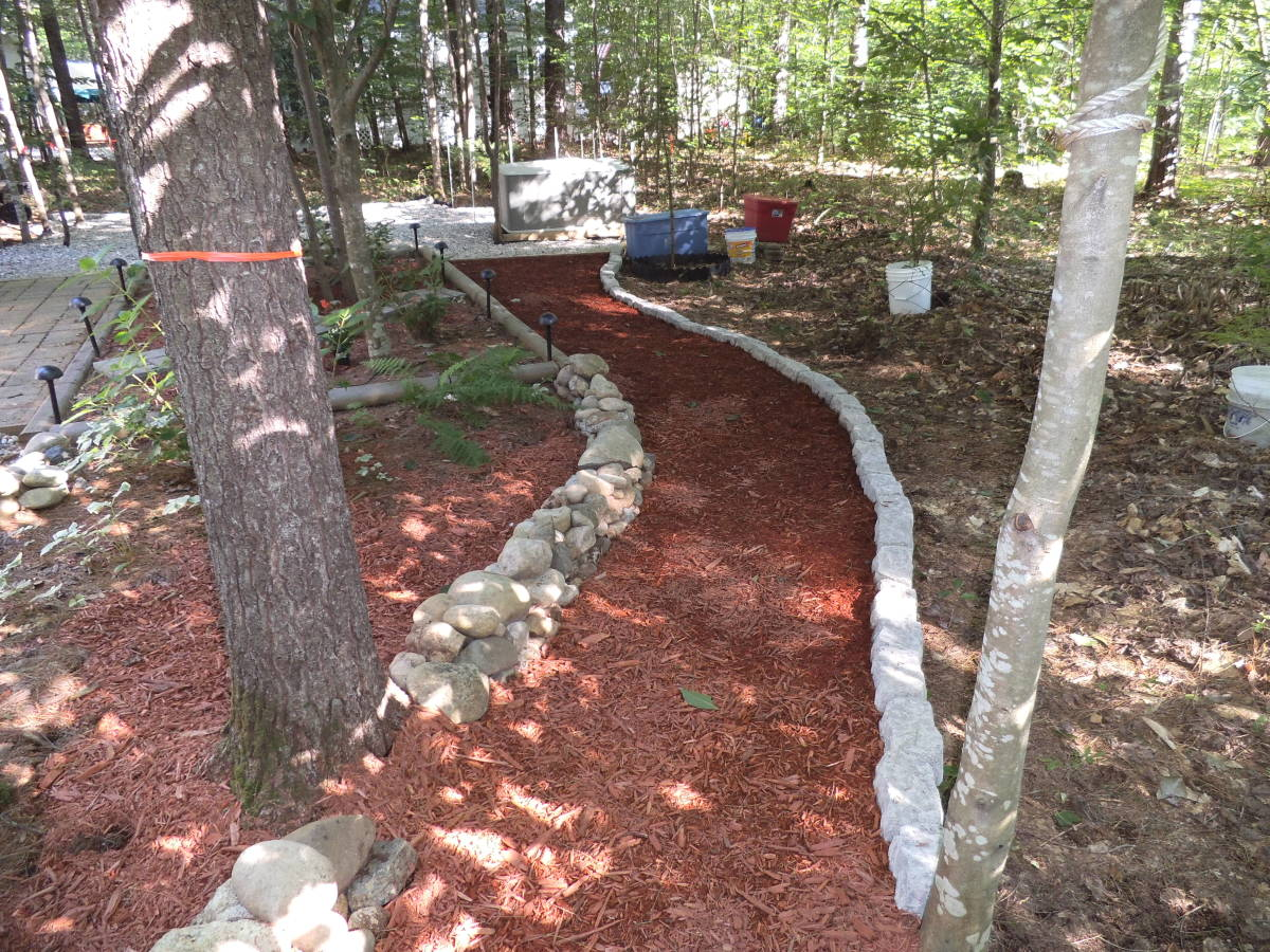 We just finished this path and put down a mulch surface that's good for all weather. This one is edged with field stone on one side and edging from the garden center on the woods side.