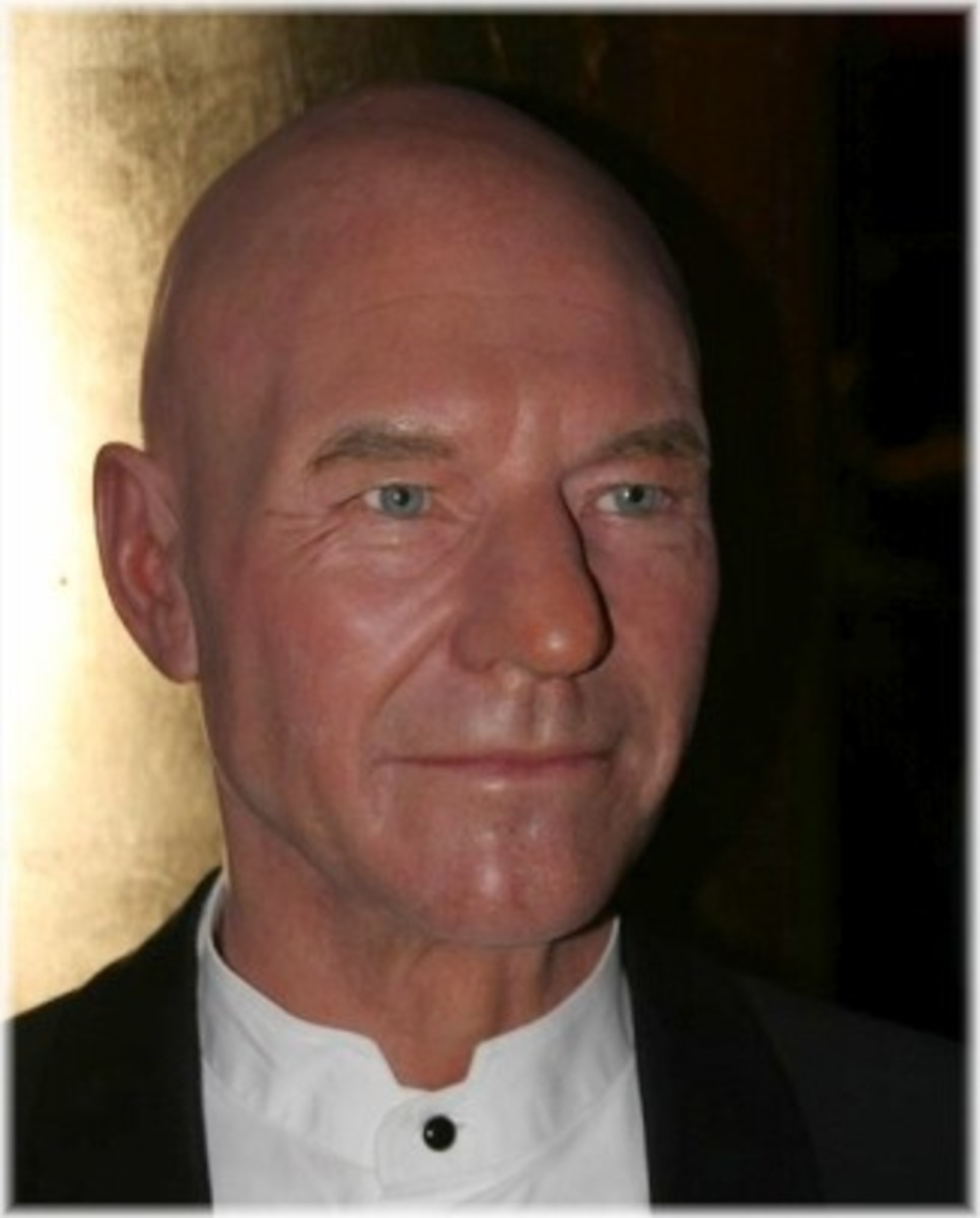 ...with piercing blue eyes and a slim, clean-shaven face. He is wearing a crisp white shirt and black jacket. Even though he is bald, he is quite handsome and distinguished.
