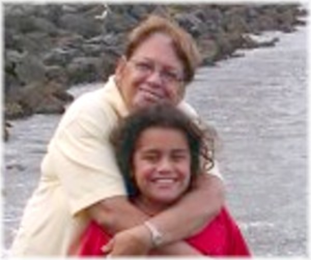 and a young girl who appears to be her granddaughter. The woman has short, reddish, wavy hair and a friendly smile. She is wearing a white blouse. She is hugging her smiling granddaughter who has long, dark curly hair and is wearing a red T-shirt.