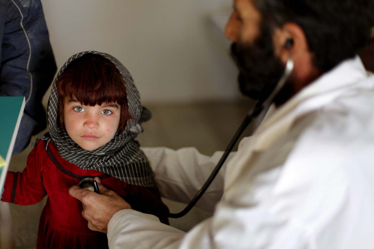 An Afghan physician listens to an Afghan girl's heart at a clinic on Camp Clark, Khowst province, Afghanistan.