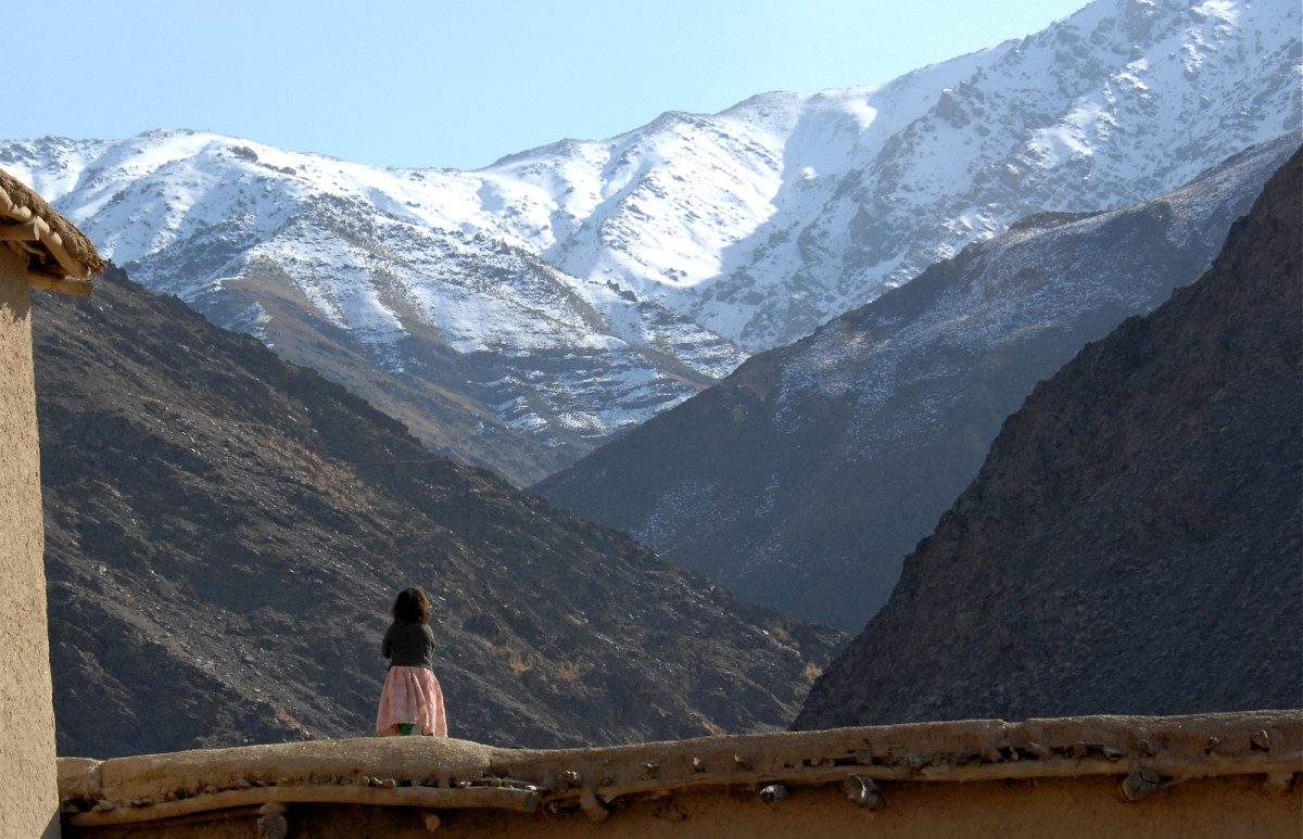 A girl looks South into the mountains surrounding Lower Kajakan Village in the Shinwari District of Afghanistan.