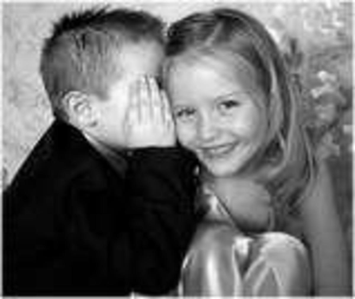 Happiness is best when shared - two children sharing a smile with the boy whispering into the blond little girls ear
