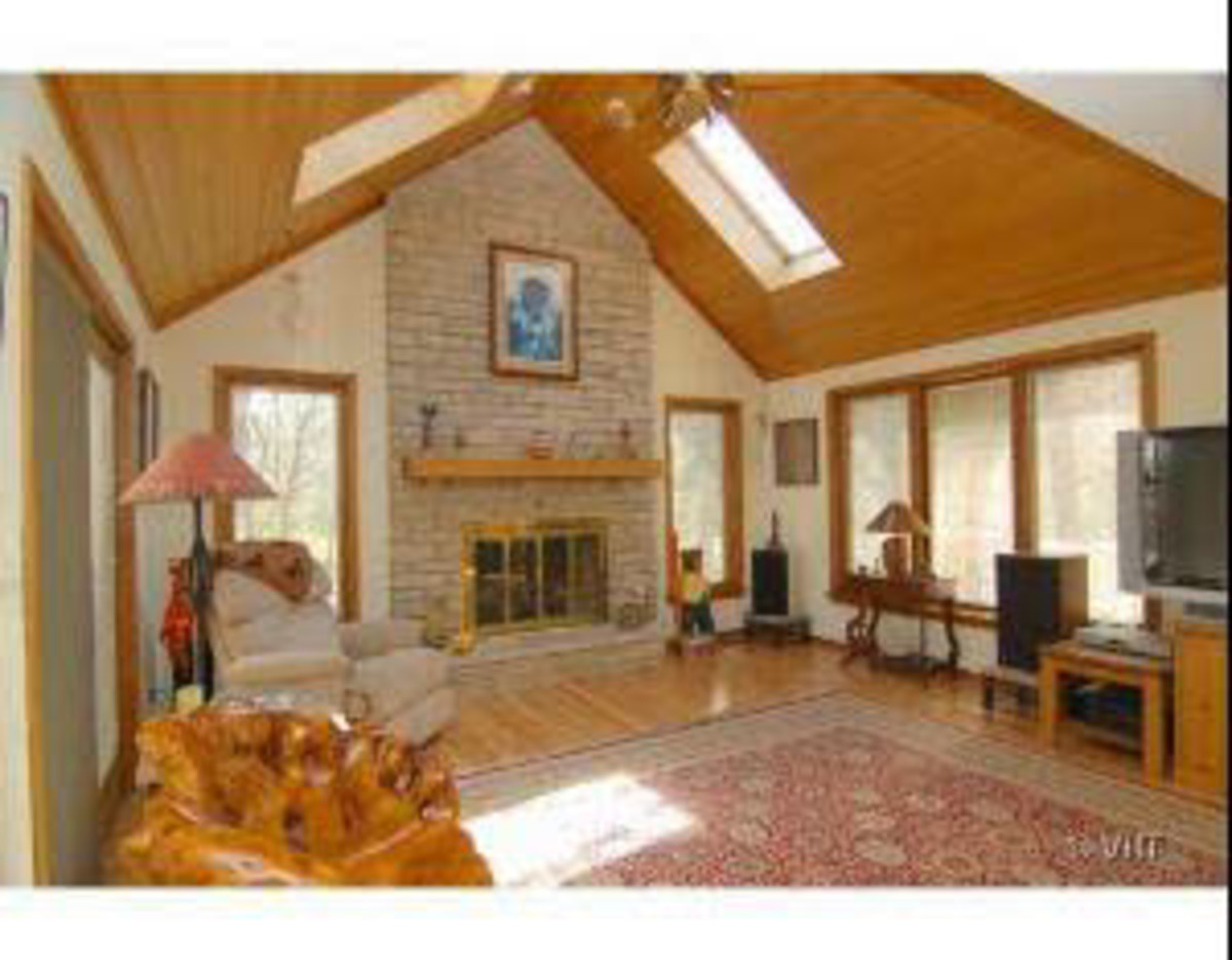 wood ceiling with skylites in great room with fireplace