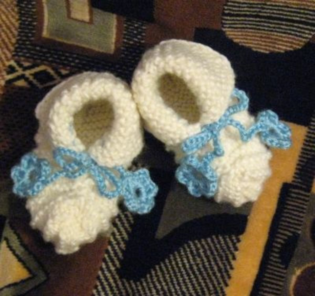 Ecru booties with crocheted flowers