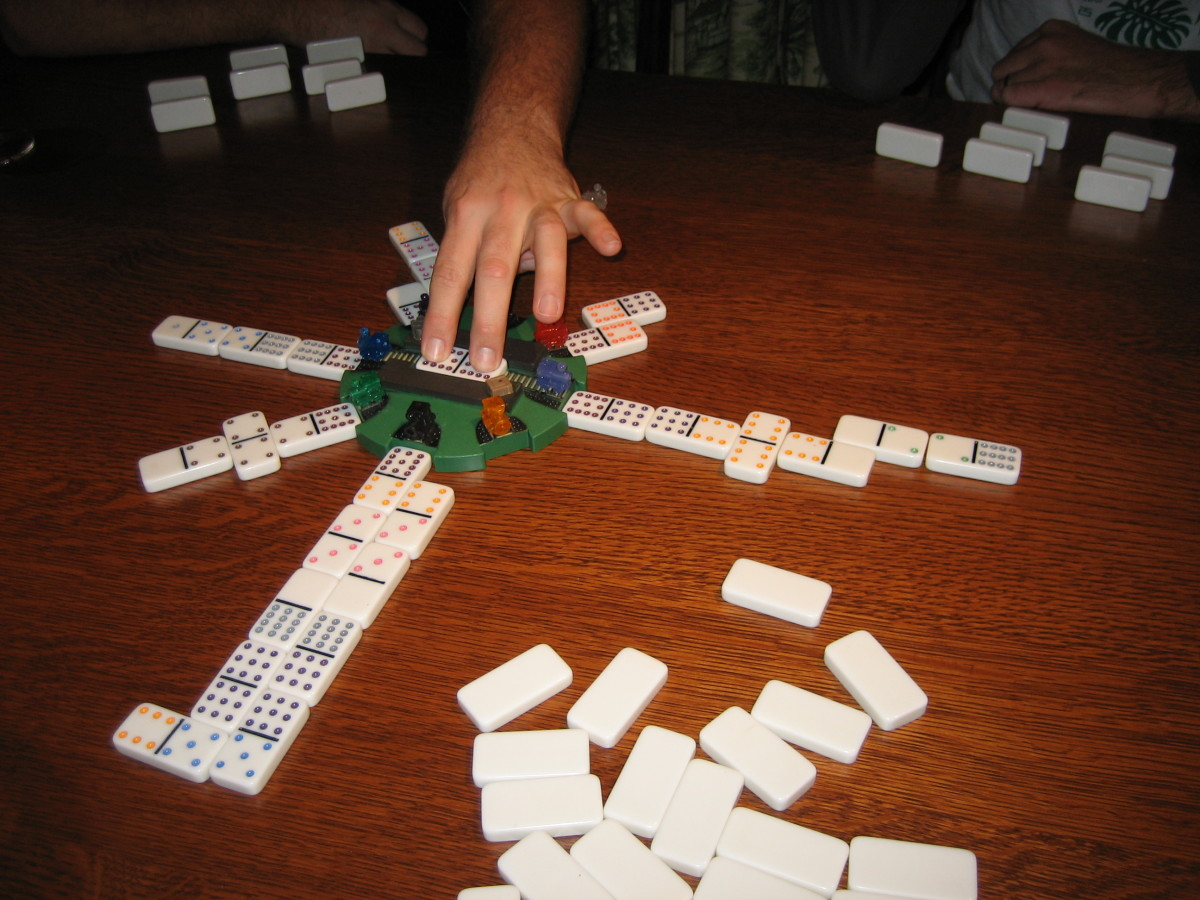 "Each player has a train, or a line of dominoes they get to play. The highest double in a player's hand starts play, and that domino is placed in the middle of the Mexican Train ""hub."""