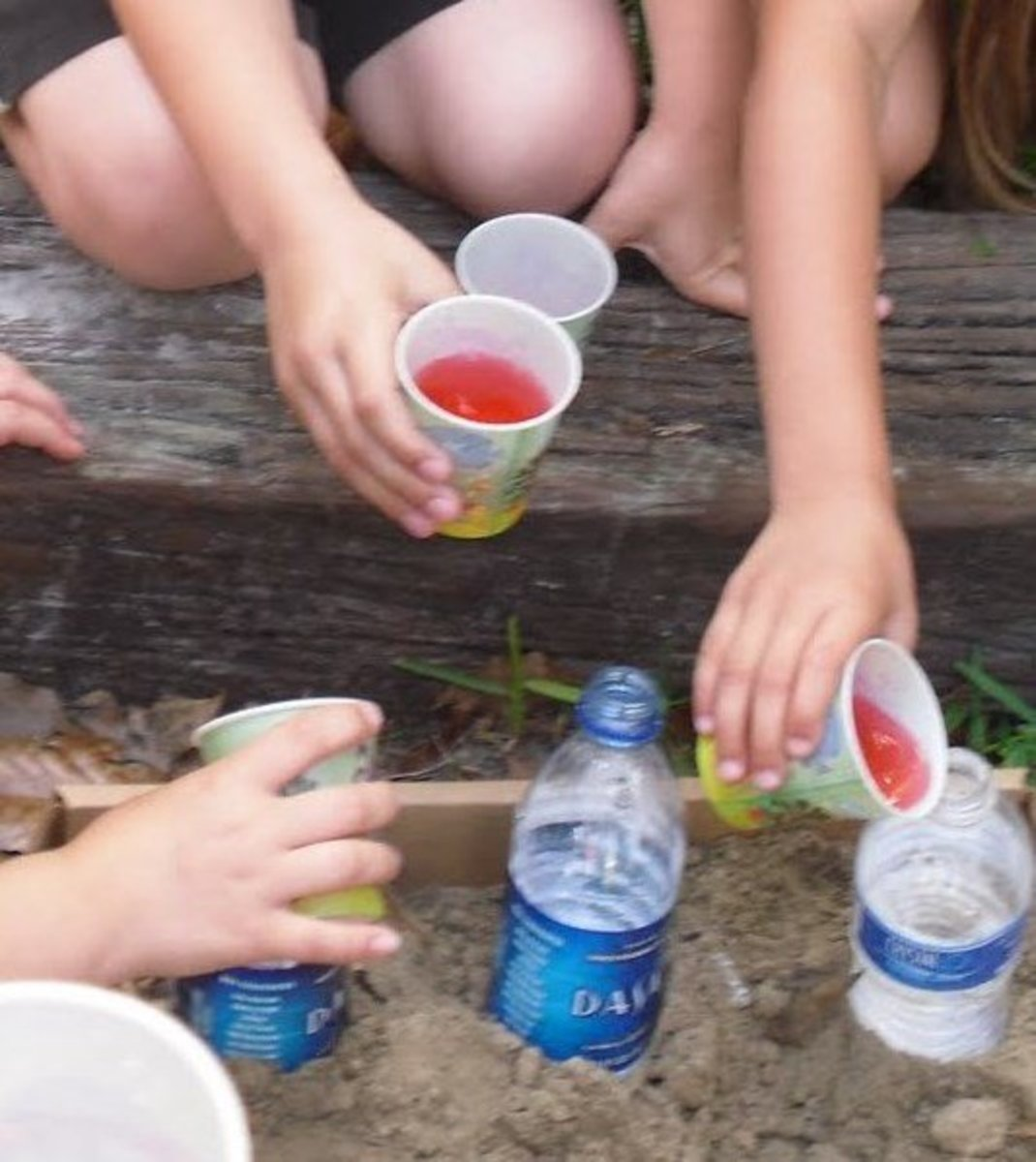 """Ring of Fire with Baking Soda/Vinegar Eruptions. You can either use a big box of sand or have individual buckets of sand.  The sand keeps the """"bottle volcanoes"""" from falling over as they erupt."""
