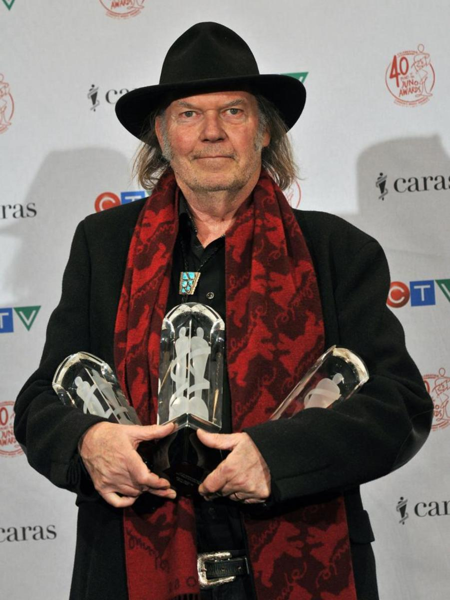 Neil Young holding his awards at the 2011 Juno Awards