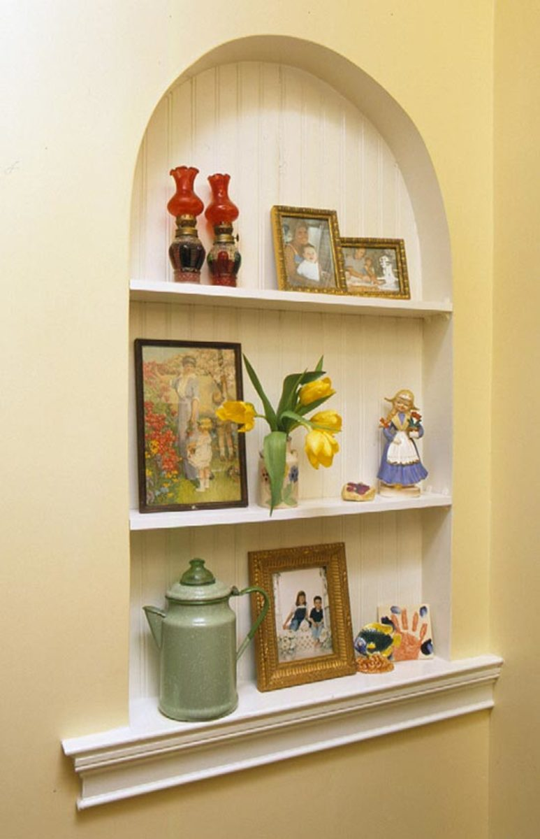 decorative alcove with shelves topped with a graceful arch on a plaster wall with bead board as the background