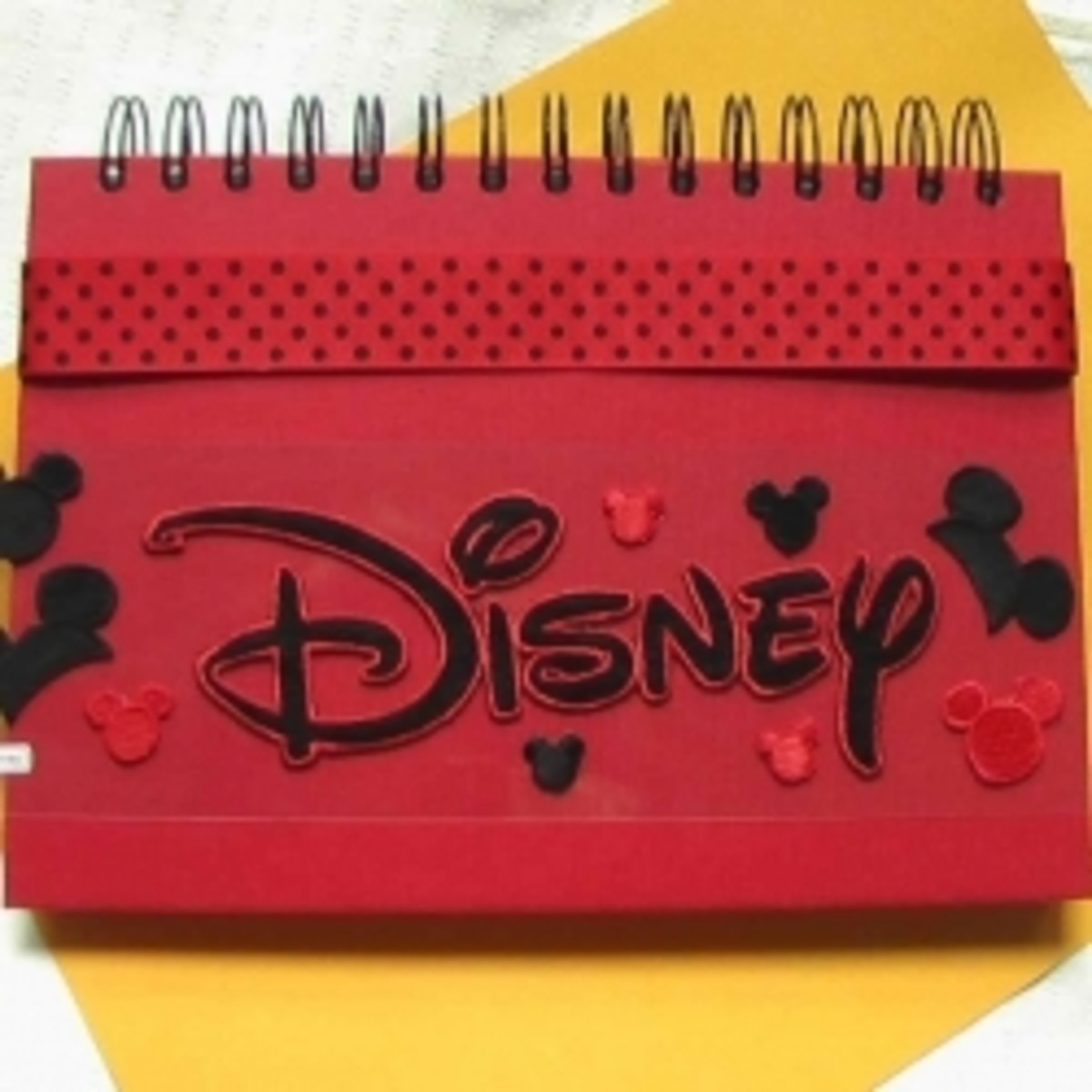 A work in progress: place your Disney stickers and ribbon decorations on the cover of your memory book before you glue them in place. You will be happy with the results if you do.